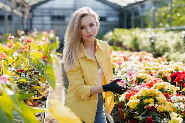 Portrait beautiful woman cares for flowers