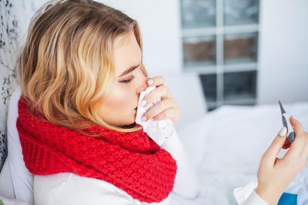 Portrait of beautiful woman caught flu, having headache and high temperature.