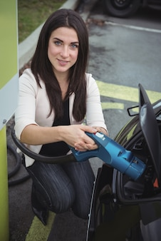 Portrait of beautiful woman charging electric car