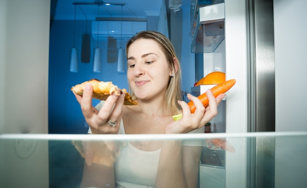Portrait of beautiful woman choosing between healthy carrot and unhealthy donut. view from inside the fridge