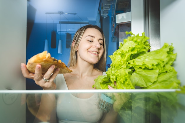 Portrait of beautiful woman choosing between pizza and fresh salad. view from inside of the fridge. concept of healthy and unhealthy food.