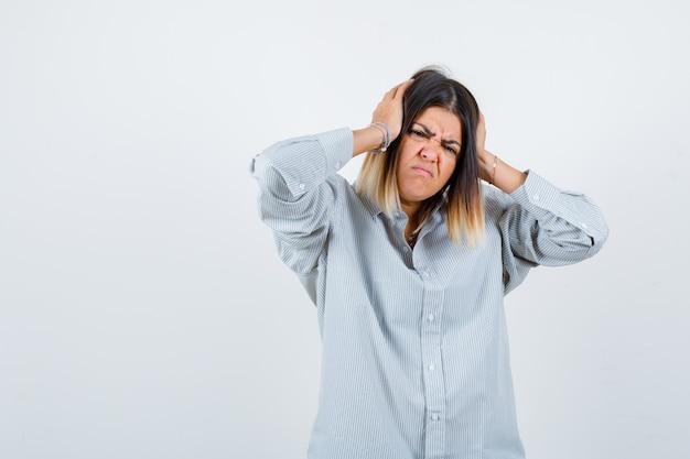 Ritratto di bella donna che stringe la testa con le mani in camicia e sembra infastidita vista frontale