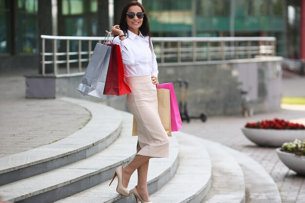 Portrait of beautiful woman in classic beige skirt and white blouse. perfect lady standing on steps near emporium with packages. shopping and fashion concept.