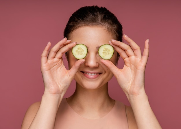Ritratto di bella donna che copre gli occhi con fette di cetriolo