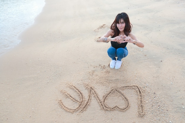Portrait of beautiful woman doing heart symbol on hands with love word on sand