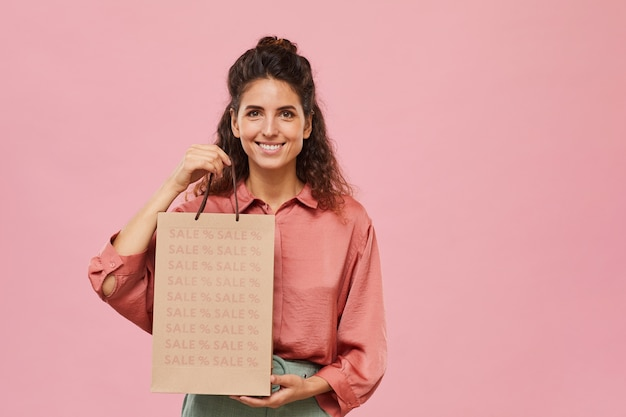 Portrait of beautiful woman doing shopping on sale she holding paper bag and smiling