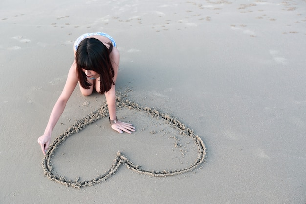 Portrait of beautiful woman drawing heart symbol on sandy beach