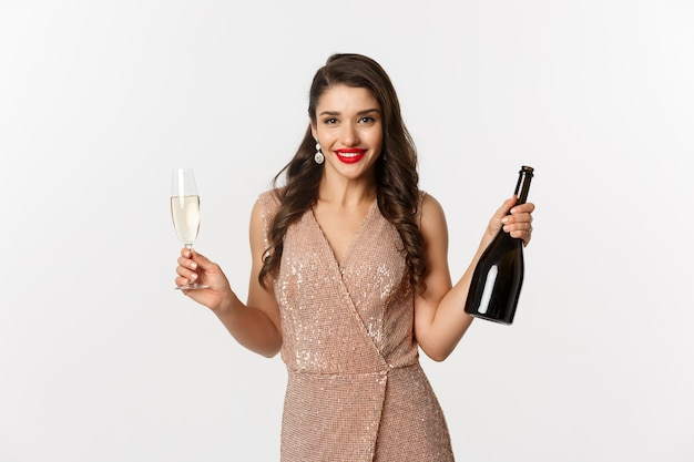 Portrait beautiful woman in dress with glass of champagne and bottle
