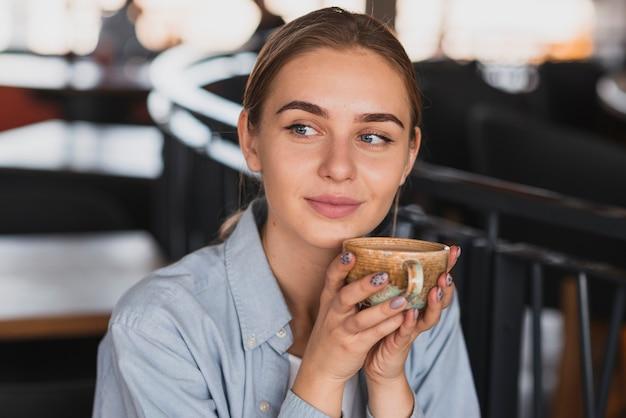 肖像画の美しい女性がコーヒーを飲む