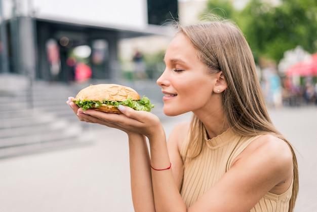 Ritratto di bella donna che mangia un gustoso hamburger per strada