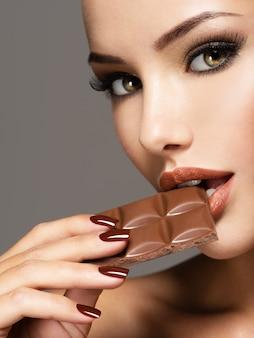 Ritratto di bella donna mangia il cioccolato dolce con gioia