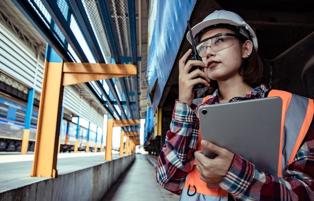 Portrait of beautiful woman engineering using walkie talkie and tablet with wear hardhat in front of train garage.