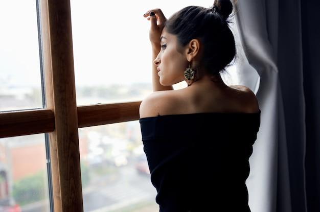 Portrait of a beautiful woman in an evening dress near the window earrings hairstyle makeup model