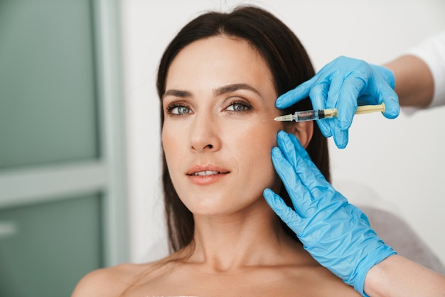 Portrait of beautiful woman getting mesotherapy treatment in face by specialist in gloves in beauty salon