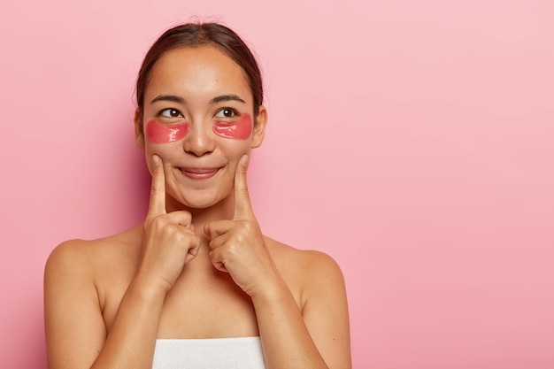 Portrait of beautiful woman has fresh skin, points at cheeks, has hydrogel patches under eyes, applies anti wrinkle collagen mask, stands wrapped in towel, looks aside, isolated on pink wall. beauty