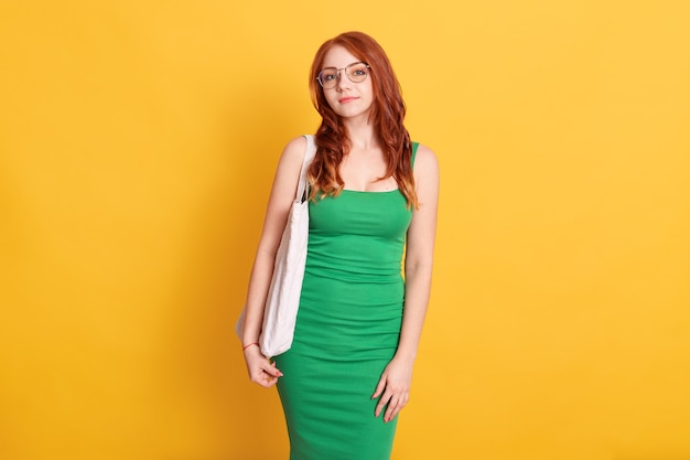 Portrait of beautiful woman hold shopping bag, , waring green dress, standing against yellow wall, lady with spectacles