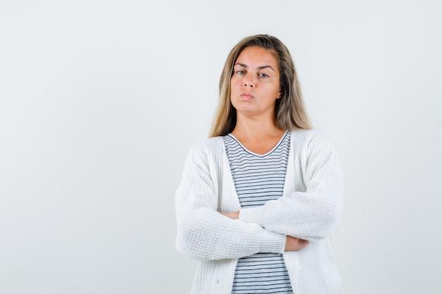 Ritratto di bella donna che tiene le braccia piegate in giacca e guardando vista frontale arrabbiata