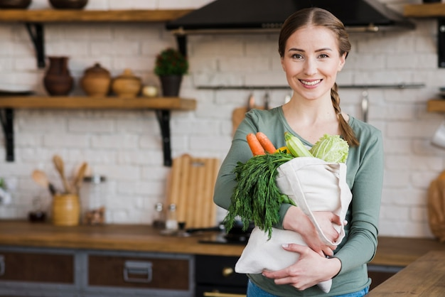 Portrait of beautiful woman holding bag with groceries