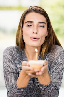 Portrait of beautiful woman holding birthday cupcake with one candle