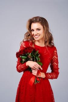 Ritratto di bella donna che tiene un mazzo di rose rosse