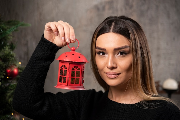 Ritratto di bella donna che tiene un giocattolo del gazebo di natale. foto di alta qualità