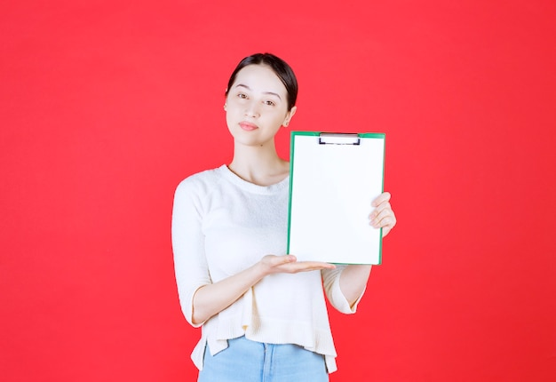 Portrait of beautiful woman holding clipboard