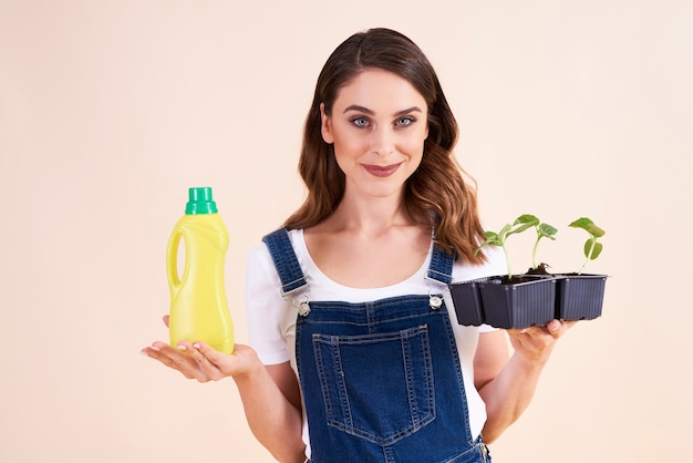 Portrait of beautiful woman holding cucumber seedling and fertilizer