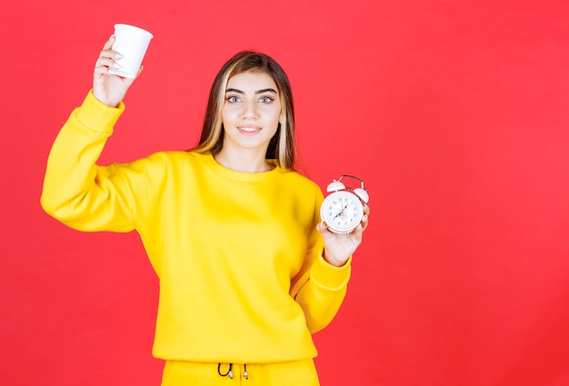 Portrait of beautiful woman holding cup and clock on red wall