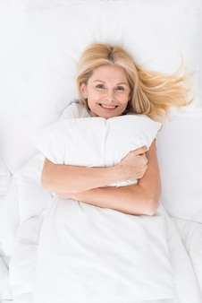 Portrait of beautiful woman holding a pillow