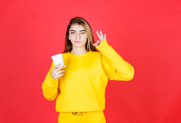 Portrait of beautiful woman holding plastic cup of tea and giving ok sign