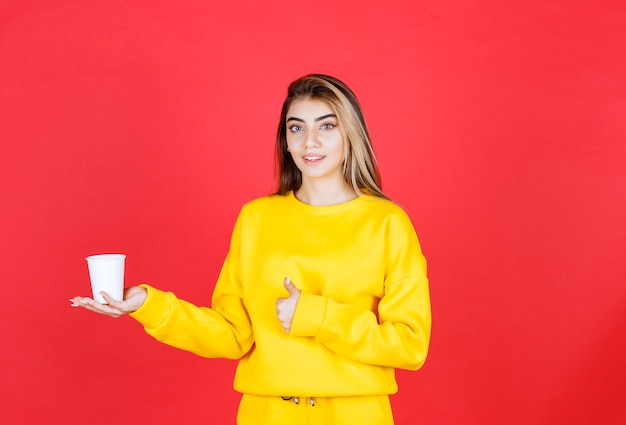 Portrait of beautiful woman holding plastic cup of tea and giving thumbs up