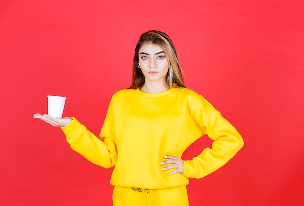 Portrait of beautiful woman holding plastic cup of tea on red wall