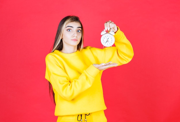 Portrait of beautiful woman holding small clock on red wall