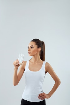 Portrait of beautiful woman holds glass of water . drink water. girl with glass of water. diet concept