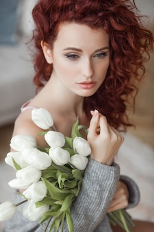 Portrait beautiful woman at home with a bouquet of flowers
