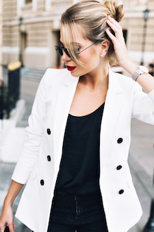 肖像画通りにサングラスで美しい女性。彼女は髪に触れて見下ろしています。