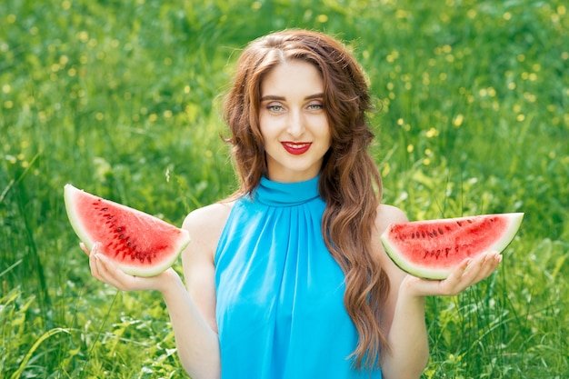 Portrait of beautiful woman is holding two slices of watermelon.
