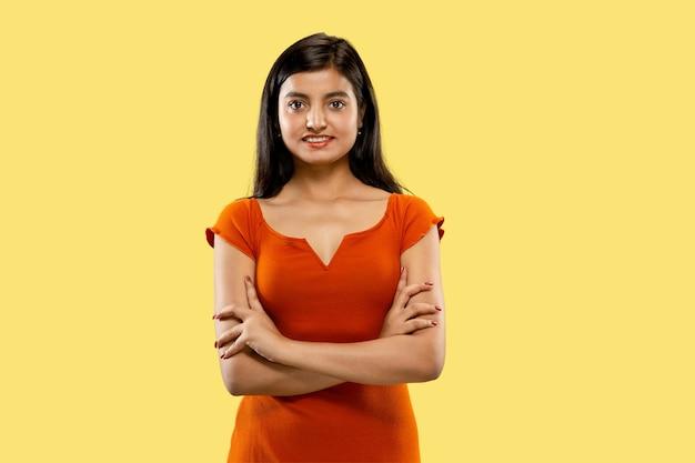 Portrait of beautiful woman isolated on yellow studio background