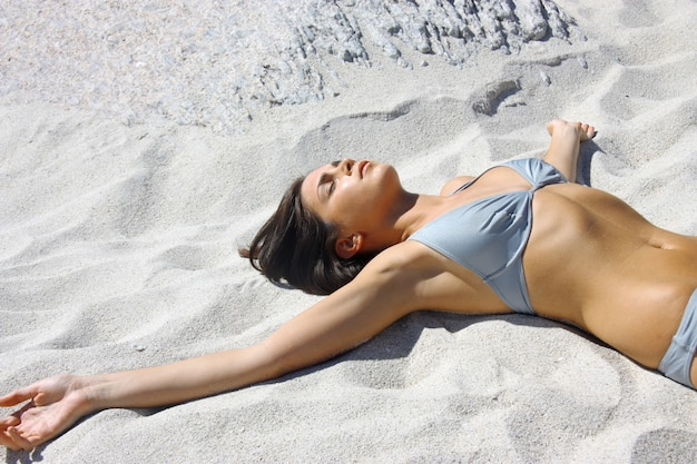 Portrait of beautiful woman laying on the sand