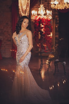 Portrait of beautiful woman in lights over christmas decor. fashion long dress and makeup.