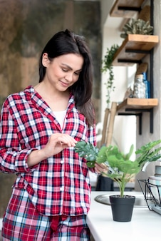 Portrait of beautiful woman looking after plant
