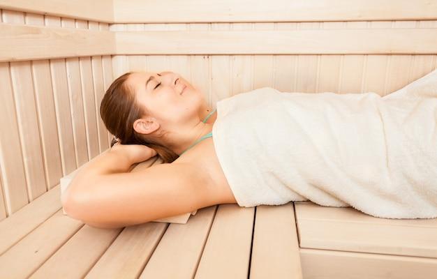 Portrait of beautiful woman lying on bench at sauna