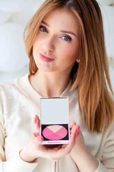 Portrait beautiful woman make up artist hold corrective sculpting palette pink blush with mirror.
