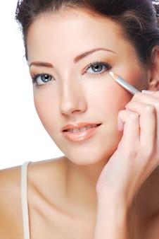 Portrait of beautiful woman making make-up using white eyeliner for eyes