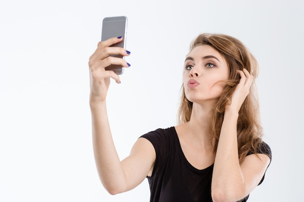 Portrait of a beautiful woman making selfie photo on smartphone isolated on a white background