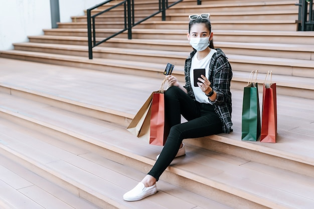 Portrait beautiful woman in mask place eyeglasses on head holding shopping bag