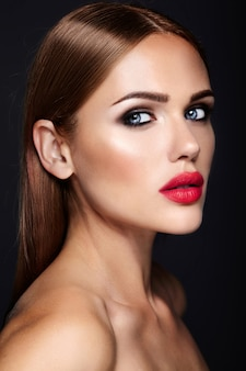 Portrait of beautiful woman model with evening makeup and romantic hairstyle. red lips