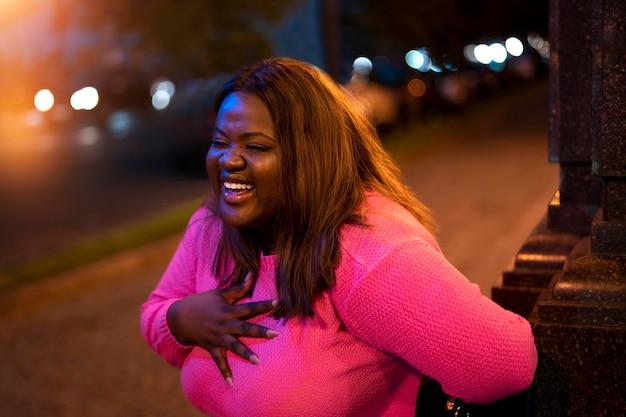 Ritratto di bella donna di notte nelle luci della città