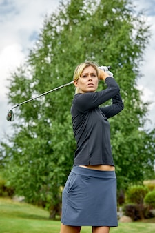 Portrait of a beautiful woman playing golf on a green field outdoors