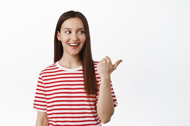 Ritratto di bella donna che punta il dito a destra, sorride e guarda il logo, racconta di grandi eventi di vendita, sconti in negozio, in piedi contro il muro bianco